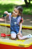Girl pours out sand in the sandbox on the playground