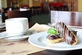 Eclairs with cream in chocolate coating on a plate and tea in cafe