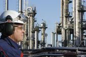 stock photo of factory-worker  - of engineer with large oil refinery in background - JPG