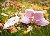 Pink baby girl boots in autumn park