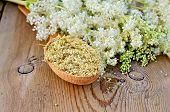 foto of meadowsweet  - Wooden spoon with dried flowers of meadowsweet a bouquet of fresh flowers of meadowsweet against a wooden board - JPG