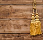 Gold rope with tassel against wooden wall