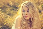 stock photo of natural blonde  - Toned Portrait of Blonde Woman on Nature Background - JPG