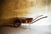 picture of wheelbarrow  - An old rusty metal wheelbarrow in a room - JPG