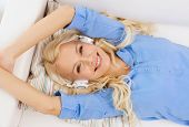 technology, music and happiness concept - smiling young girl lying on sofa in headphones at home