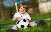 Blond Boy Of 3 Playing Soccer With Football On Football Field