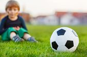 Blond boy of 4 playing soccer with football on football field outdoors. Selective focus on ball.