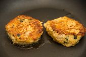 picture of crab-cakes  - Two crab cakes sauteing in a frying pan with hot oil - JPG