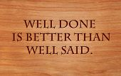 Well done is better than well said - motivational quote by Benjamin Franklin on wooden red oak backg