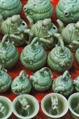Traditional Ceramic Oriental Teapots And Cups On A Market Bench.