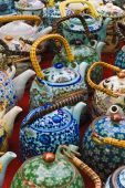Colorful Ceramic Oriental Teapots On Chinese Market Bench.