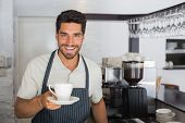 Portrait of a young smiling male barista holding cup of coffee at the caf�?�©