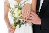 Mid section of newly wed couple with flower bouquet showing wedding rings over white background