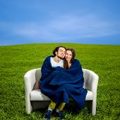 Young Couple Sitting And Relaxing On The Couch At The Green Field With Blue Sky