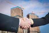 Businessman Handshake With Building Construction Background