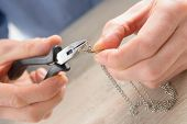 foto of pliers  - Man repairing or creating jewelry silver chain with pliers - JPG