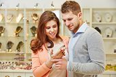 Smiling couple looking at bracelet and other jewelry at jeweler
