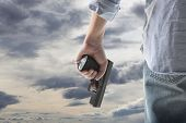 image of pistol  - Man Holding Gun against an sky background - JPG