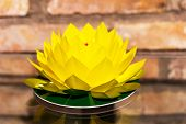 Lotus Flower Of Bright Yellow Paper On Brick Wall Background
