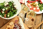 white wine and different snacks on wooden table