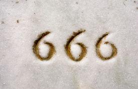 stock photo of antichrist  - Macro of numbers 666 engraved on granite headstone - JPG