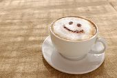 stock photo of chocolate spoon  - Coffee cappuccino with foam or chocolate smiling welcome happy face in restaurant or hotel - JPG