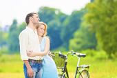 Young Affectionate Caucasian Couple Resting Together In The Park Area With Bicycle.