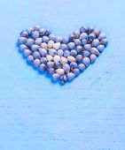 Coix seed in the shape of a heart on a blue board