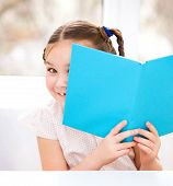 Little Girl Is Playing With Book