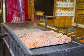 Traditional czech trdelnik baking on a street stand of Prague