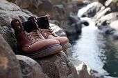 Limited Focus Old Hiking Boots In Front Of Waterfall