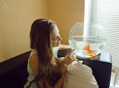 pretty woman playing with goldfish at home