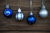 Four Decorated Christmas Balls On Wood