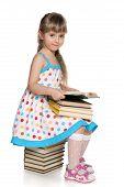 Little Girl Reading On The Pile Of Books