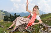 Young blonde woman in Bavarian dirndl smiles and waves.