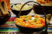 stock photo of chickpea  - curry chickpea with cauliflower and vegetables on a dark wood background. tinting. selective focus on the middle of curry