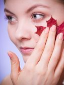 Skin Care. Portrait Of Young Woman Girl With Red Maple Leaf.