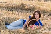 Teen girl with a basket of apples in  field
