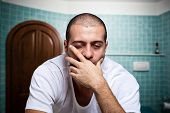stock photo of deprivation  - Portrait of a tired man looking in the mirror in his bathroom - JPG