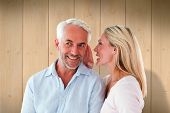 Woman whispering a secret to husband against wooden planks