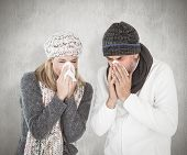 Sick couple in winter fashion sneezing against weathered surface