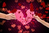 pic of broken hearted  - Hands holding two halves of broken heart against digitally generated girly heart design - JPG