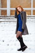 Full length portrait of young pretty redhead woman in blue dress and grey coat at winter outdoors