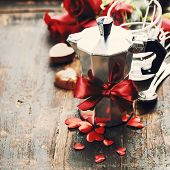 Valentine composition with coffee maker and flowers on wooden background