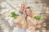 Happy couple carrying paper grocery bags against light circles on bright background