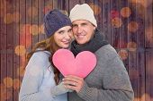 Happy couple in warm clothing holding heart against close up of christmas lights