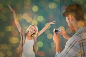 Man taking photo of his pretty girlfriend against close up of christmas lights