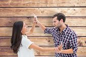 Fearful brunette being overpowered by boyfriend against wooden planks background