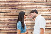 Angry man shouting at upset girlfriend against wooden planks background