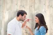 Angry couple pointing at each other against pale wooden planks